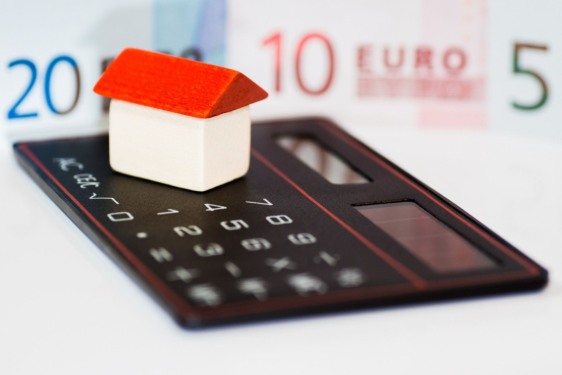 Casa tejado rojo y calculadora
